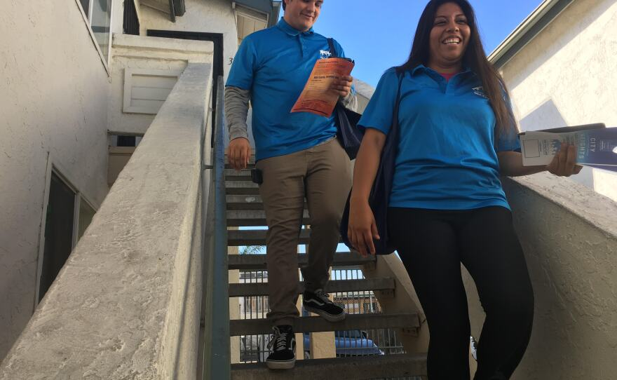Dennis Smith, 18 (left), and Rosa Olascoaga Vidal, 22, descend the stairs of an apartment complex where they contacted a voter, Nov. 5, 2018.