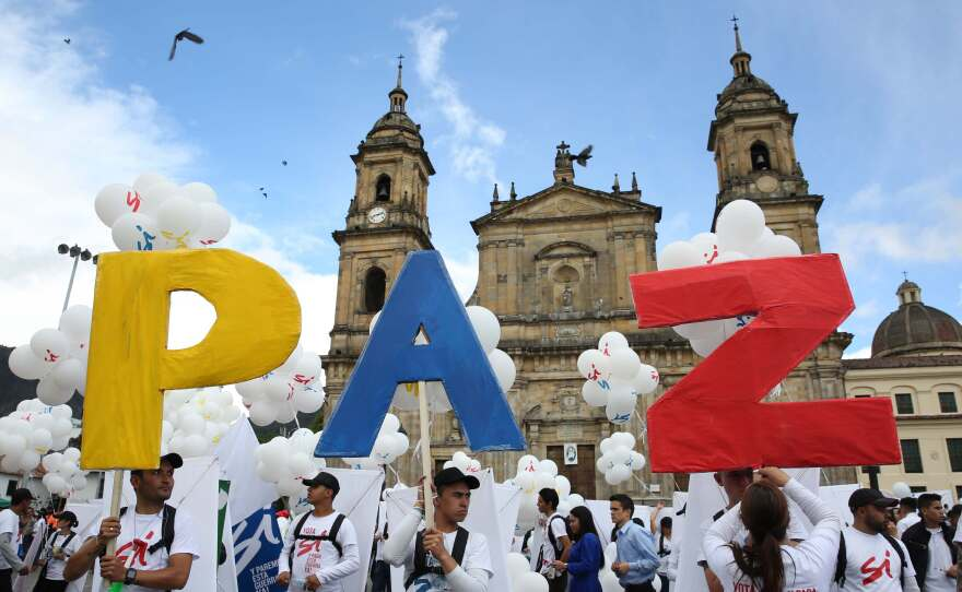 """Colombians in the capital, Bogota, hold up the letters for """"peace"""" in Spanish on Monday. The Colombian government and FARC rebels signed a peace agreement, marking an end to the last war in the Western Hemisphere. Colombia's civil war lasted more than 50 years and Latin America has had civil wars for the past six decades."""