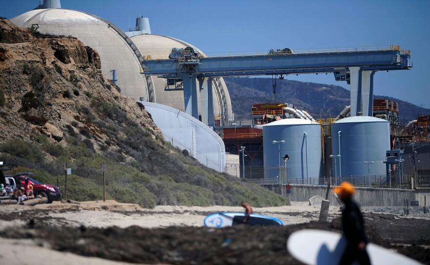 Surfers walk along a beach nearby the San Onofre nuclear power plant, July 19, 2012.
