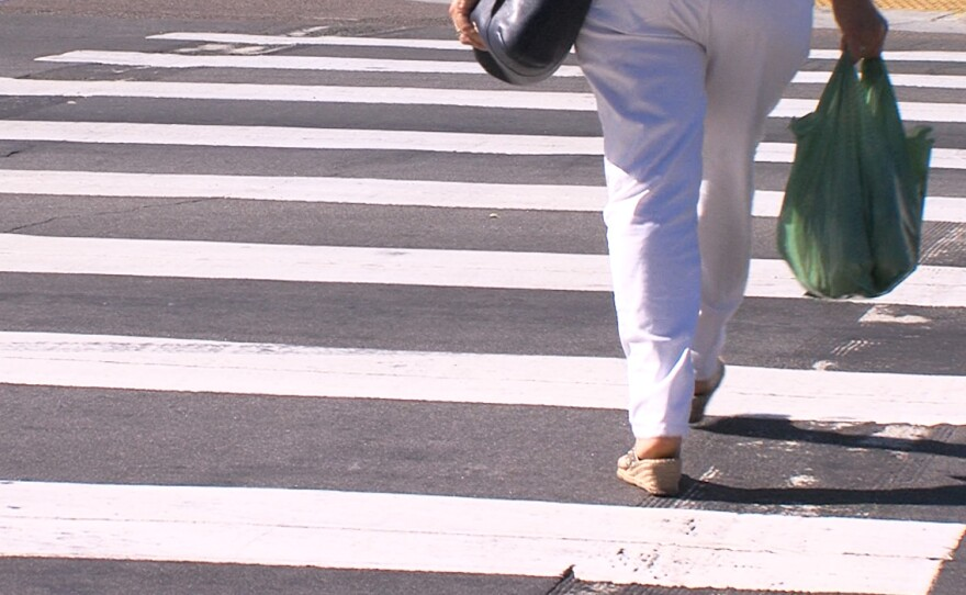 A pedestrian crosses a street in City Heights, June 19, 2017.