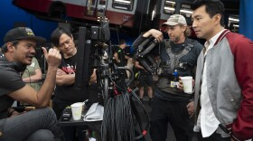 """Filmmaker Destin Cretton (far left) on the set of Marvel's """"Shang-Chi and the Legend of the Ten Rings"""" with actor Simu Liu (far right)."""