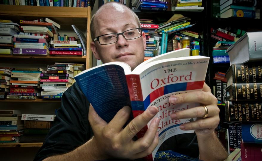 """Grant Barrett, co-host of the public radio show """"A Way With Words,"""" leafs through a dictionary in this undated photo."""