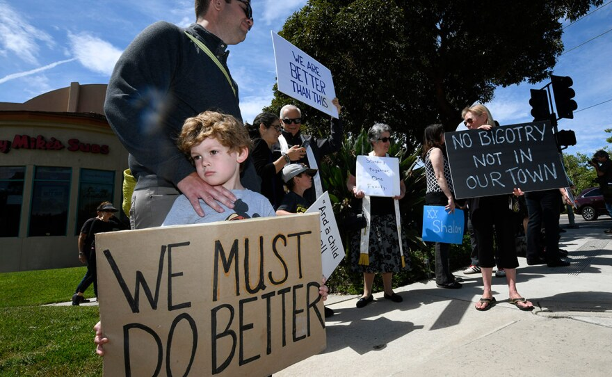Kyle Fox, 4, and his father Brady Fox hold a sign at a vigil held to support the victims of Chabad of Poway synagogue shooting, Sunday, April 28, 2019, in Poway, Calif. A man opened fire Saturday inside the synagogue near San Diego as worshippers celebrated the last day of a major Jewish holiday.
