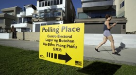 In this March 3, 2020 file photo, a woman runs on a path by a polling place during primary elections in San Diego.