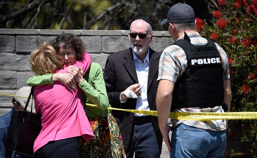 Two people hug as another talks to a San Diego County Sheriff's deputy outside of the Chabad of Poway synagogue, Saturday, April 27, 2019, in Poway, Calif. A man opened fire inside the synagogue near San Diego as worshippers celebrated the last day of a major Jewish holiday.