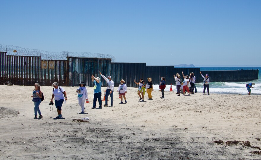 People march alongside the U.S.-Mexico border fence at a protest in June 2021 at Border Field State Park.