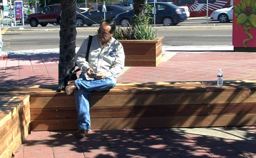 A resident sits on a bench at the corner of Euclid and Imperial avenues in San Diego, Oct. 31, 2015.