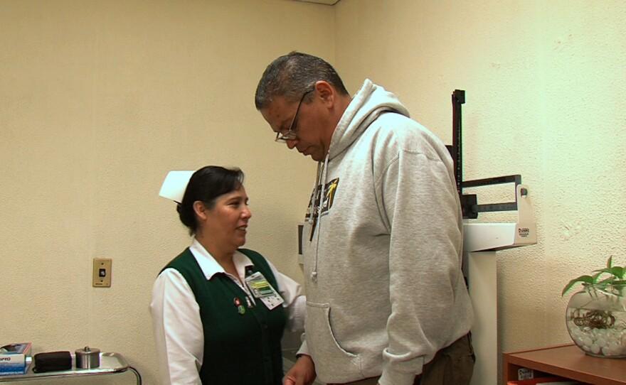 A nurse at Clinic No. 27 in Tijuana weighs Armando Huerta, a diabetes patient, Nov. 7, 2014.