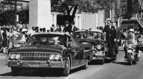 In this Nov. 22, 1963, file photo, seen through the foreground convertible's windshield, President John F. Kennedy's hand reaches toward his head within seconds of being fatally shot. About 90% of the government records surrounding the assassination have been released but the release of the remaining records have now been delayed.