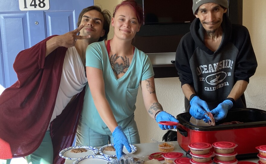 Undated photo of three Oceanside Homeless Resource motel shelter clients packing up meals.