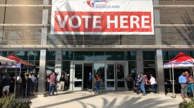 """A """"Vote Here"""" sign hangs on the San Diego County Registrar Of Voters Office, Nov. 6, 2018."""