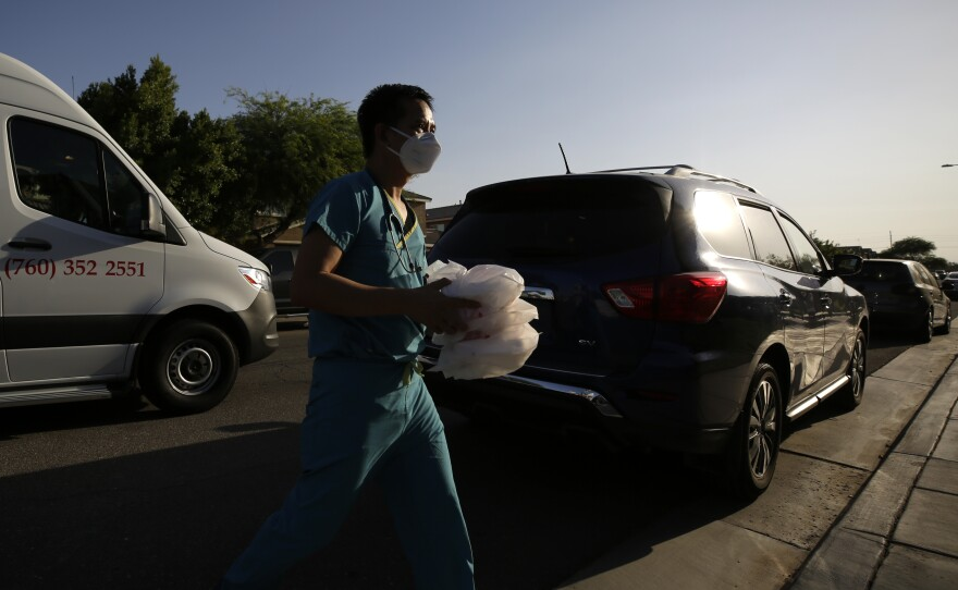 """Dr. Tien Vo carries food for a family quarantining after testing positive for the coronavirus Thursday, July 23, 2020, in Calexico, Calif. Vo moved to Imperial Valley 10 years ago. He says he stayed because people are friendly and appreciative. He sees happiness in their eyes when they greet him. """"They really need a doctor here,"""" he says from the front seat of a company van between house calls. """"They're not very hard to please. They chat with me. They text me every day."""""""