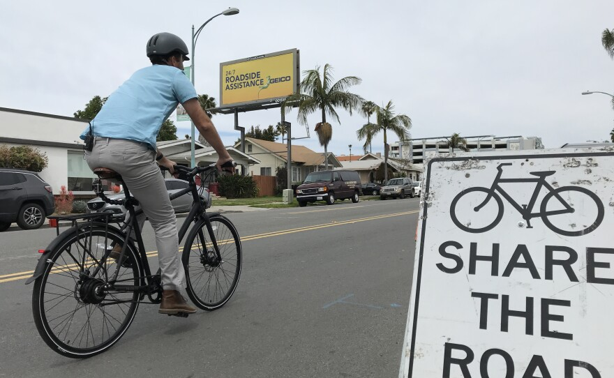 """Matt Stucky rides his bike up 30th Street in North Park past a sign that reads """"Share the road,"""" March 27, 2019."""