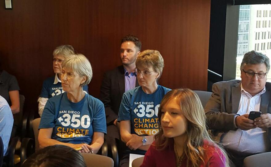Members of the environmental group San Diego 350 watch the SANDAG board meeting on the regional transportation plan, Oct. 9, 2015.