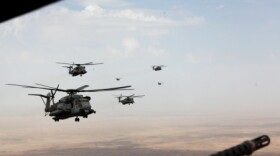 Marine Corps and Royal Air Force helicopters fly in formation after departing Camp Bastion, Afghanistan, Oct. 27, 2014.