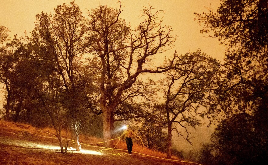 A firefighter lays hose around the Foothills Visitor Center while battling the KNP Complex Fire in Sequoia National Park, Calif., on Tuesday, Sept. 14, 2021.