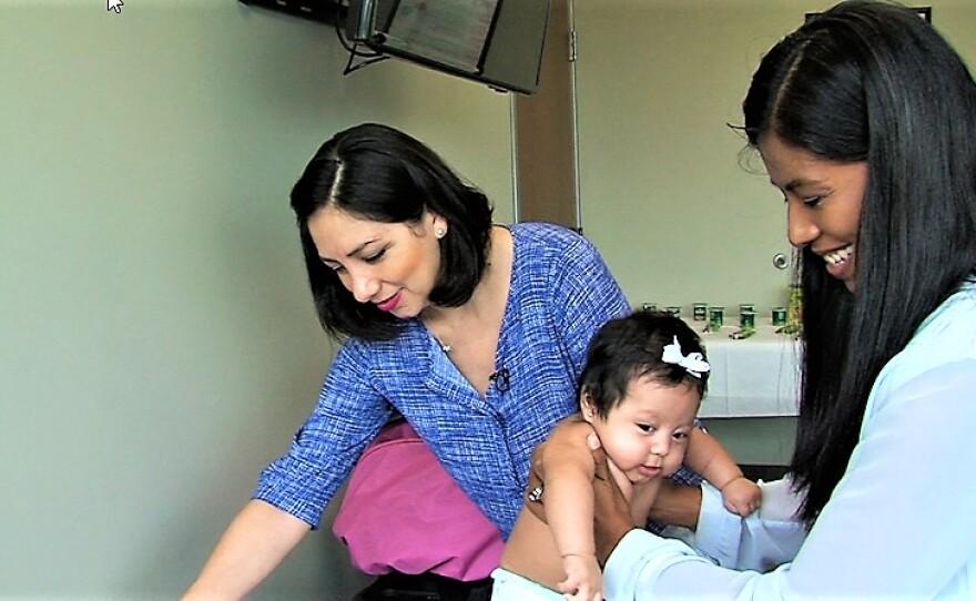 At a San Ysidro Health Center clinic in Chula Vista, Mayra Moreno looks on as her baby daughter, Ambar, is examined by Dr. Yelennia Palacios.