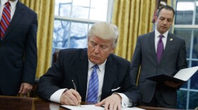 President Donald Trump signs an executive order to withdraw the U.S. from the 12-nation Trans-Pacific Partnership trade pact agreed to under the Obama administration in the Oval Office of the White House in Washington, Monday, Jan. 23, 2017.