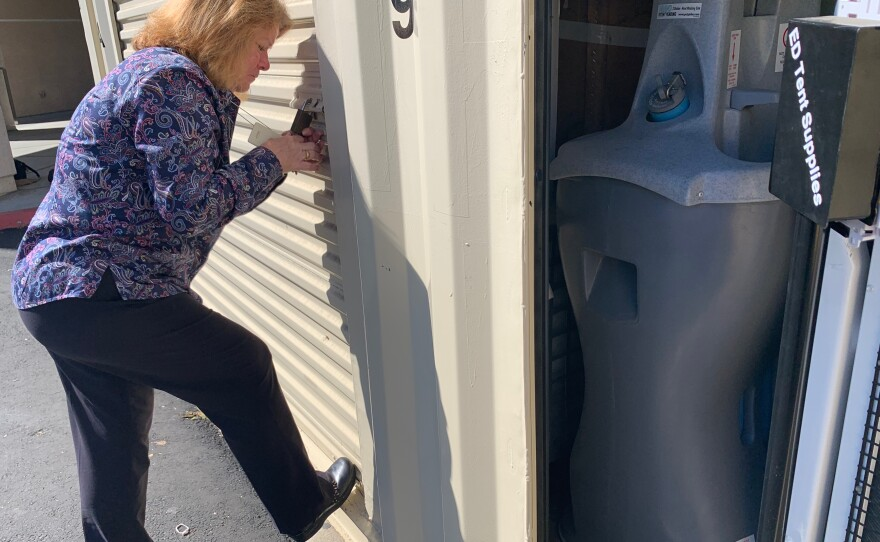 Kathy Muth, senior safety management specialist at Sharp Chula Vista Medical Center, uses a key in the lock of a roll-top garage behind the hospital, Oct. 24, 2019. The adjacent open storage space houses emergency equipment.