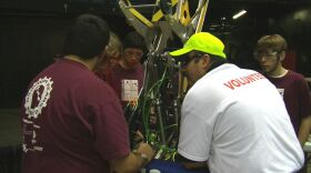 Students from Kearny High School make adjustments to their robot with a FIRST Robotics volunteer working with to get the robot ready and qualified for the eighth annual San Diego competition, March 6, 2014.