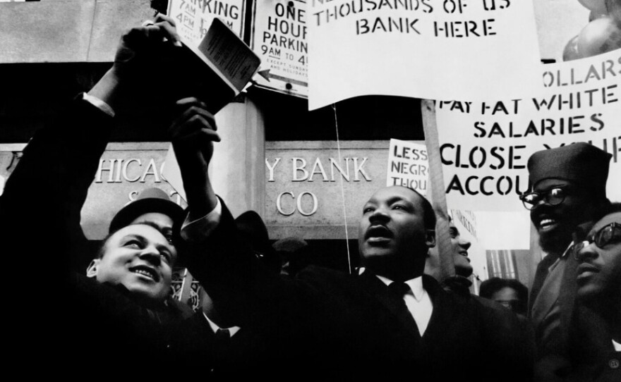 Richard Lawrence and Martin Luther King, Jr. are pictured burning bank notes.