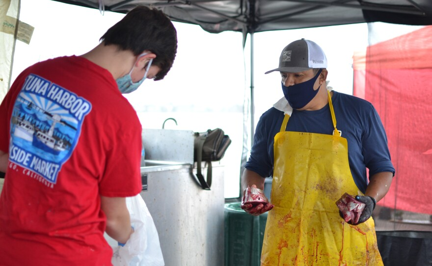 A fisherman has freshly butchered a fish at the Tuna Dockside Harbor Market in downtown San Diego, May 9, 2020.