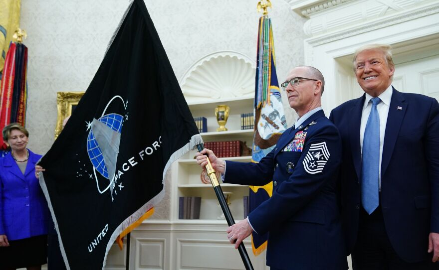 President Trump presedisplays the U.S. Space Force flag in the Oval Office last May. The new command plans to move its headquarters from a temporary location in Colorado to Alabama in 2023.