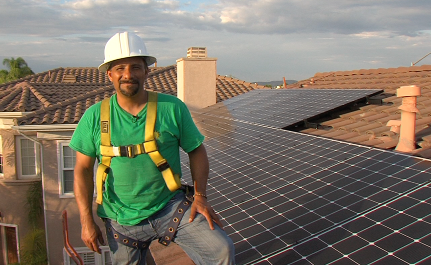 Phil Salas, project manager for the solar panel installation company Home Energy Systems, stands in front of panels he and his crew installed on a San Diego home, Oct. 12, 2015.