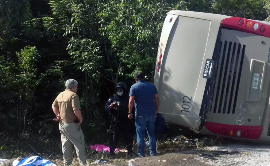 Police and paramedics at the scene of a tourist bus crash in eastern Mexico Tuesday. Most of the passengers on board were had arrived aboard cruise ships and were going to view Mayan ruins.