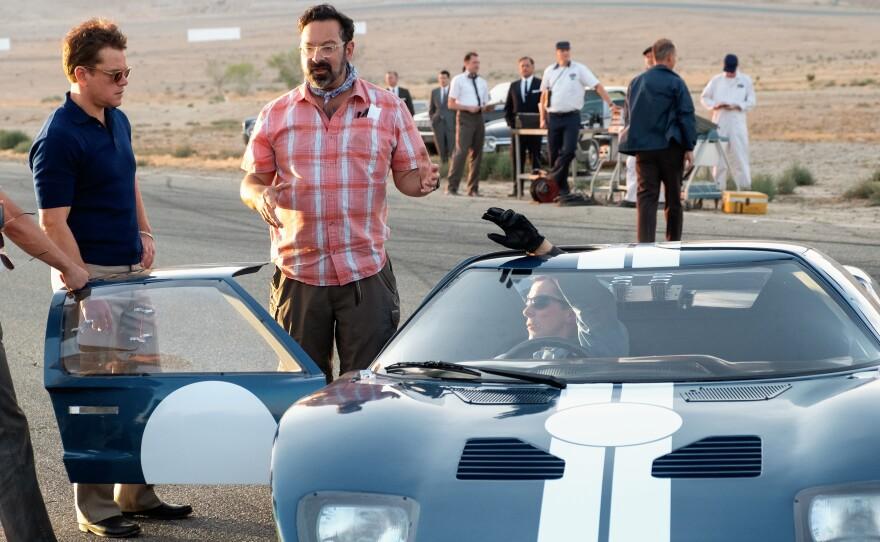 "Director James Mangold (center) on the set of ""Ford v Ferrari"" with actors Matt Damon and Christian Bale."