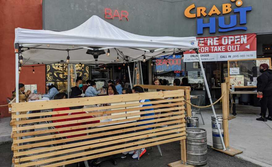 Customers seated outside in the parking lot at Crab Hut restaurant in Kearny Mesa, Feb. 15, 2021.