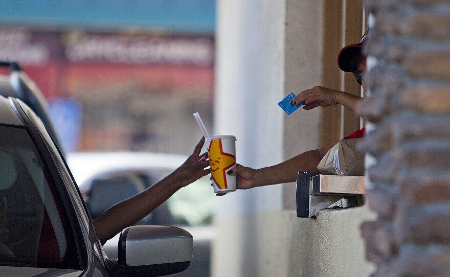 A Carl's Jr. employee serves a customer through a drive-thru window in San Diego on Sept. 13, 2013.
