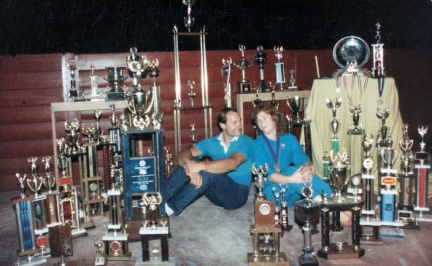 Carolyn and Allen Fisher surrounded by their trophies. They once donated 400 trophies to a thrift store.