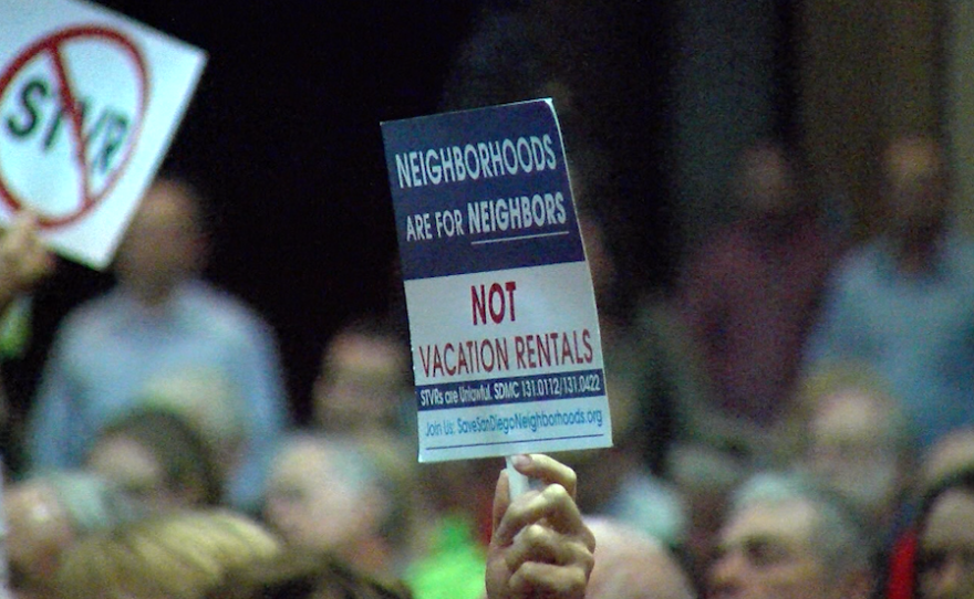 """A hand holds up a sign reading """"Neighborhoods are for neighbors, not vacation rentals"""" at a San Diego City Council meeting, Nov. 1, 2016."""