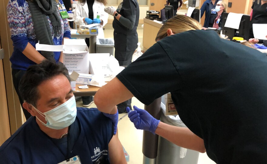 Diego Varras, an employee of Kaiser Permanente San Diego, receives a COVID-19 vaccine at Zion Medical Center. Dec. 16, 2020.