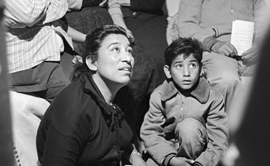 Migrant mother Maria Moreno became the first farmworker woman in America to be hired as a union organizer. Surrounded by farmworkers and their children at a house meeting, Maria listens and takes notes. 1960