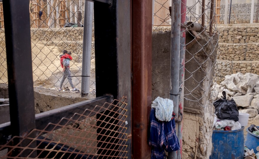 A father holds his child outside of the Embajadores de Jesus Shelter in Tijuana on April 14th, 2021. The shelter accepts around a hundred people each day who were returned to Mexico by Customs and Border Protection.