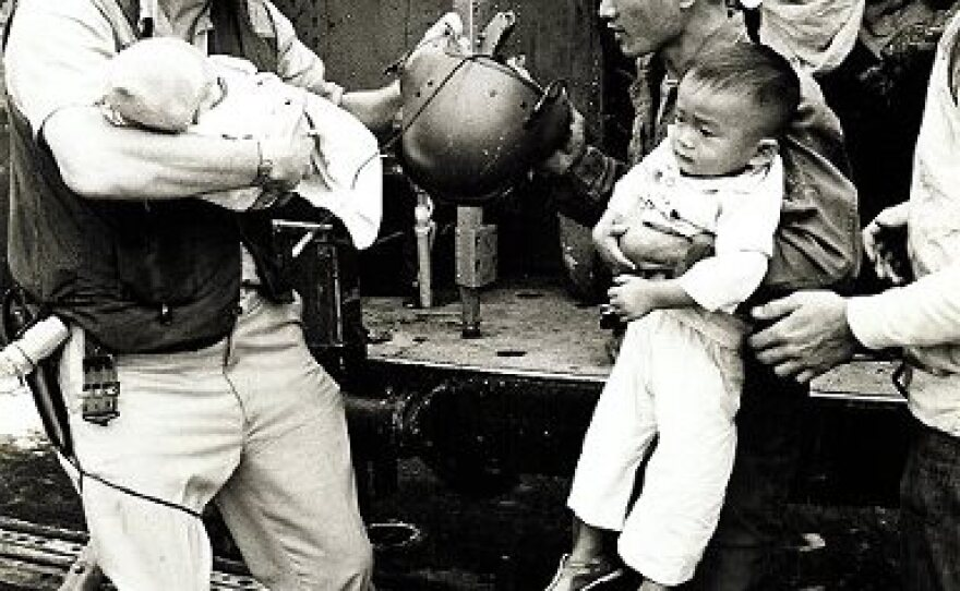 A sailor helps a man and a baby in Operation Frequent Wind on the USS Midway, April 29, 1975.