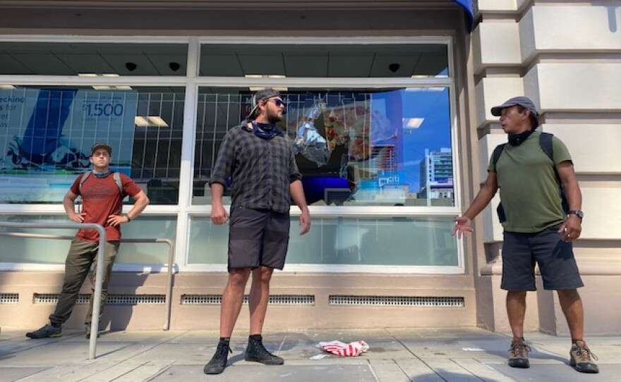 Three men protecting a window that was shattered by a protestor who was asked to leave in downtown San Diego, May 31, 2020.