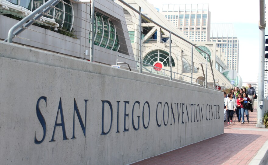 A group waits to cross Harbor Drive in front of the San Diego Convention Center.