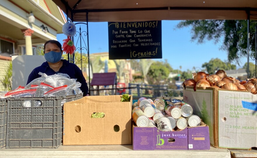 Araceli Mauricio volunteers at a pop-up food donation stall in Sherman Heights. She says a lot of people in the community have started coming here since the pandemic started, Nov. 20, 2020.