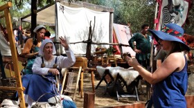 A festival attendee uses her phone to record The Wolves Of Odin reenactment group encampment at the 2019 Vista Viking Festival.