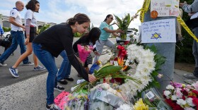 A group of Poway residents bring flowers and cards to a memorial outside of the Chabad of Poway synagogue, Sunday, April 28, 2019, in Poway, Calif. A man opened fire Saturday inside the synagogue near San Diego as worshippers celebrated the last day of a major Jewish holiday.