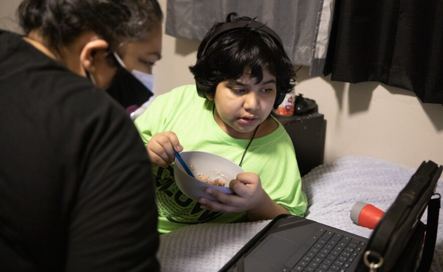 Patty Mendoza checks in with her son, Erik Martinez, while he attends school online from a bedroom in their Imperial Beach apartment, March 23, 2021.