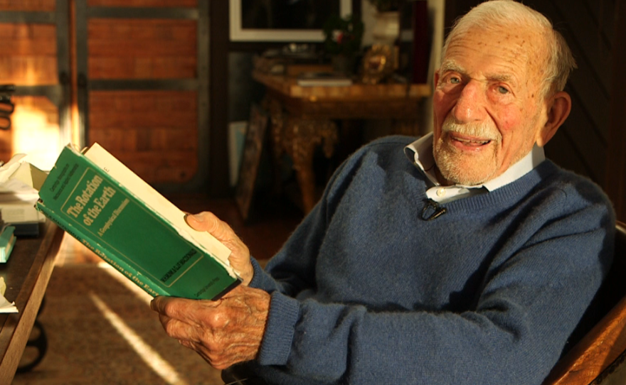 Walter Munk holds a copy of The Rotation of the Earth, a book he co-wrote in 1960, March 9, 2016.