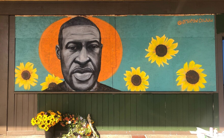 A mural of George Floyd, painted by artist Chloe Becky, covers the plywood boards on the shattered storefront of a beauty college in La Mesa on June 2, 2020.