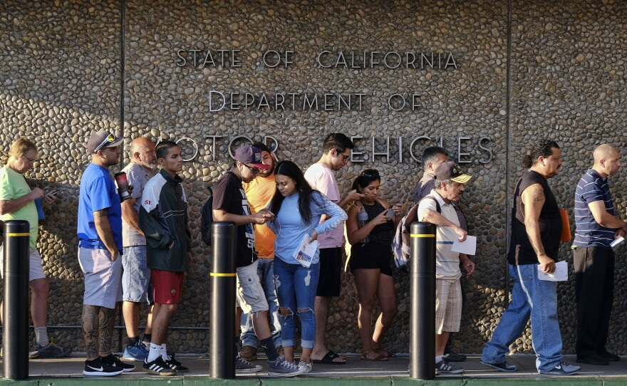 People line up at the California Department of Motor Vehicles prior to opening in the Van Nuys section of Los Angeles on Tuesday, Aug. 7, 2018.