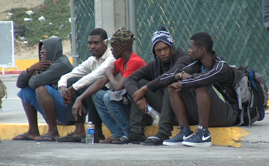 A group of Haitians on the way to the U.S. sits on a curb in Tijuana, Sept. 20, 2016.