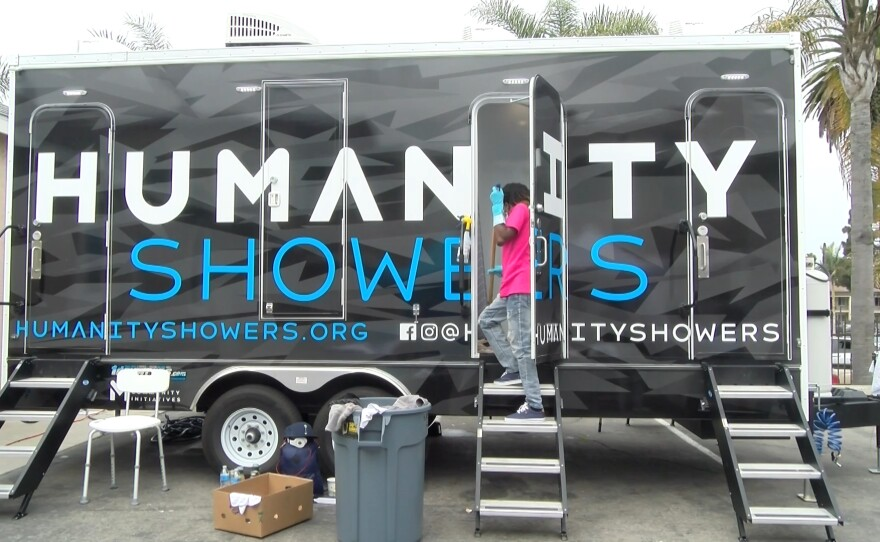 A volunteer sanitizes a shower stall from the Humanity Showers trailer in between guests. May 12, 2021.