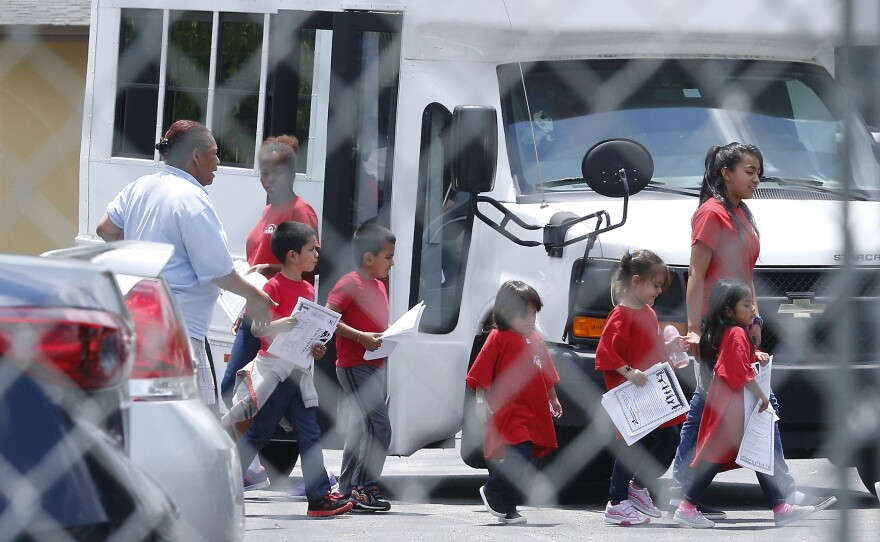 Migrant children walk off a bus at the Catholic Charities' Msgr. Bryan Walsh Children's Village in Cutler Bay, Fla., June 21, 2018.